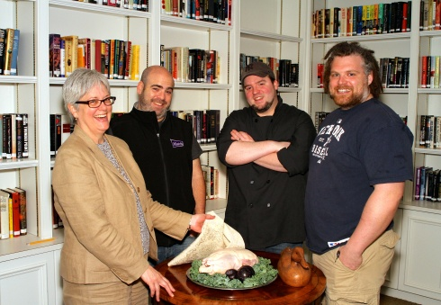 Grace Weber, executive director of Founders Hall, presents a fresh Pekin duck to Chefs Matt Storch, Forrest Pasternack and Jeff Taibe, who will be competing in Battle of the Chefs to benefit Founders Hall on Sunday, June 1, 4 -7pm, at Founders Hall.