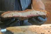Pitmaster Nestor holding up his Crispy Pork Belly at Hoodoo Brown BBQ in Ridgefield